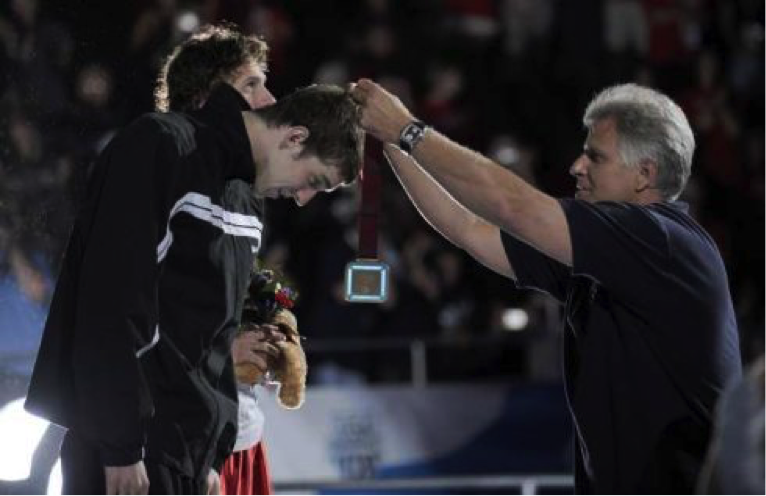Seven-time Olympic gold medal winner Mark Spitz places a medal on Michael Phelps after the 200m individual medley during the USA 2008 Olympic swim trials