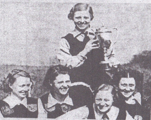 Enid Ellis holds up the English Leagues Cup won by Cheadle Heath in 1939