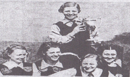 Enid Ellis holds up the English leagues Cup won by Cheadle Heath in 1938